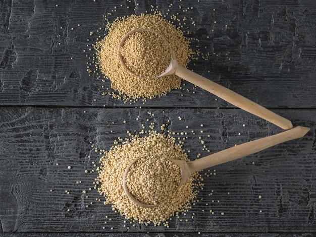 Sementes de amaranto e quinoa e duas colheres de pau em uma mesa. comida sem glúten.
