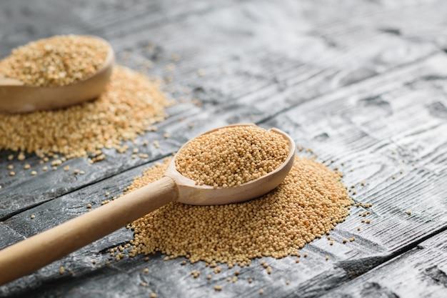 Sementes de amaranto e quinoa e duas colheres de pau em uma mesa de madeira escura. comida sem glúten.