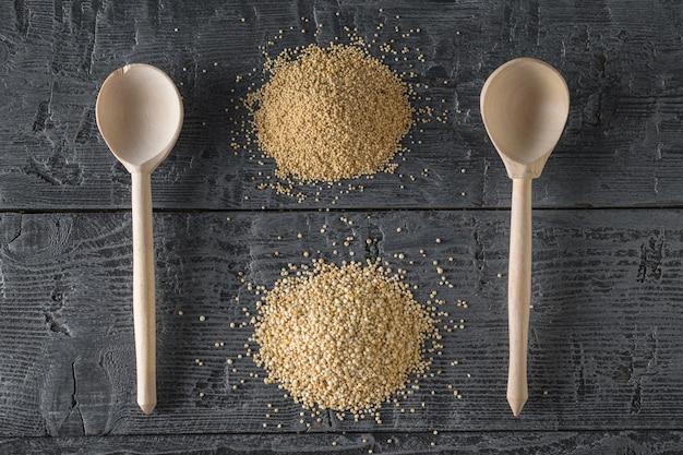 Sementes de amaranto e quinoa e duas colheres de pau em uma mesa rústica. comida sem glúten.