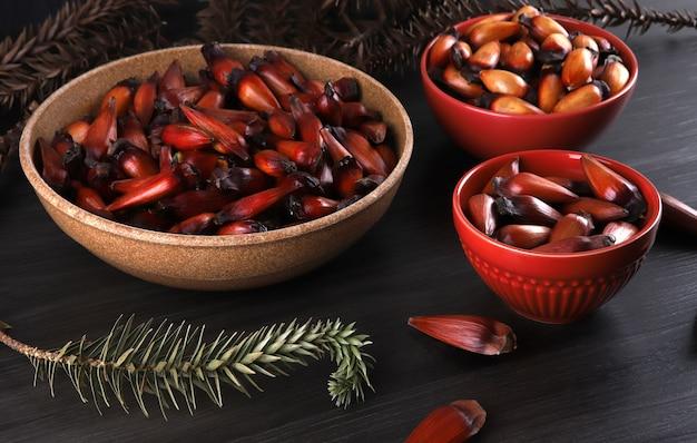 Sementes de araucária típicas usadas como condimento na culinária brasileira no inverno. nozes de pinhão brasileiro em tigela de madeira marrom e vermelha na mesa de madeira cinza.