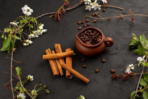 Sementes de café com canela e flores brancas no chão escuro