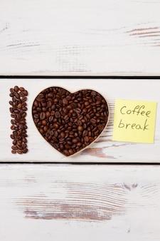 Sementes de café dispostas em forma de coração. eu amo a pausa para o café. pranchas de madeira brancas na superfície.