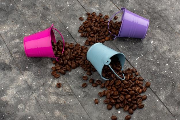 Sementes de café marrom vista superior dentro de vasos multicoloridos sobre o cinza de madeira rústico