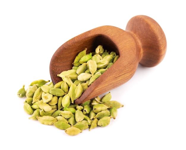 Sementes de cardamomo em colher de madeira, isoladas em branco. pilha de vagens de cardamomo verde.