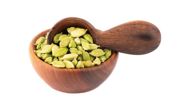 Sementes de cardamomo em uma tigela de madeira e uma colher, isoladas no branco. pilha de cardamomo verde.