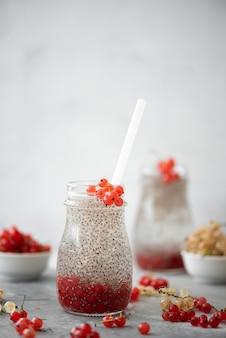 Sementes de chia com água mineral e frutas em garrafas de vidro