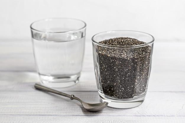 Sementes de chia preta em uma tigela de vidro e água na qual estão embebidas. com uma colher de metal.