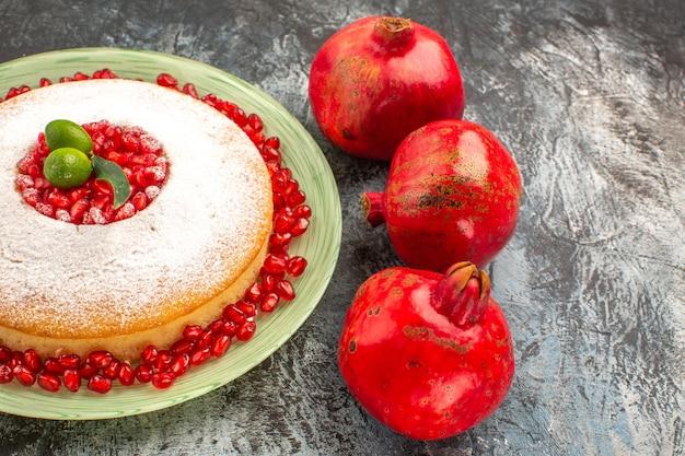 Sementes de close-up lateral de romãs romãs maduras e o bolo apetitoso na tigela