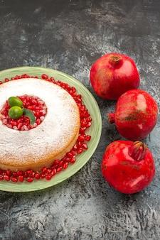 Sementes de close-up lateral de romãs três romãs vermelhas e o bolo apetitoso