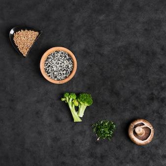 Sementes de coentro; sementes de gergelim; brócolis; cebolinha picada e cogumelo no pano de fundo preto textura