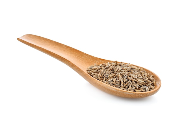 Sementes de cominho em colher de madeira