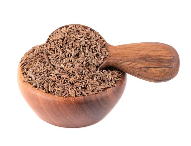 Sementes de cominho em uma tigela de madeira e uma colher, isoladas no branco. sementes de cominho ou cominho.