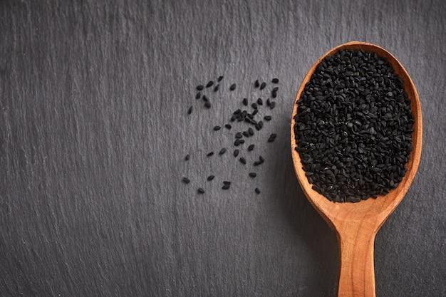 Sementes de cominho preto e uma colher de pau em uma mesa de madeira.