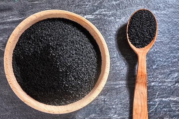 Sementes de cominho preto e uma colher de pau em uma mesa escura.