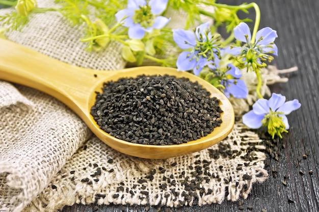 Sementes de cominho preto em uma colher no saque, galhos de kalingi com flores azuis e folhas verdes em um fundo de placa de madeira escura