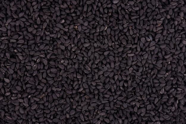 Sementes de cominho preto. nigella sativa. closeup fundo.