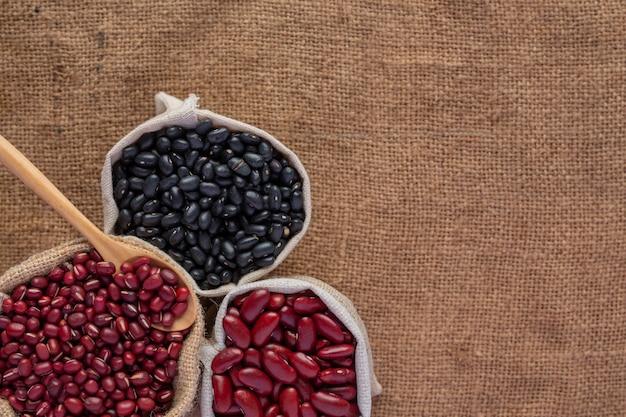 Sementes de feijão de duas cores colocadas sobre um piso de madeira marrom.
