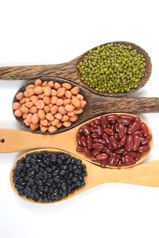 Sementes de feijão (feijão preto, feijão vermelho, amendoim e feijão mungo) úteis para a saúde em colheres de madeira.