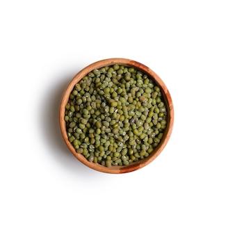 Sementes de feijão verde seco em uma tigela de madeira, ingredientes alimentares na culinária asiática, isolados no fundo branco. vista do topo