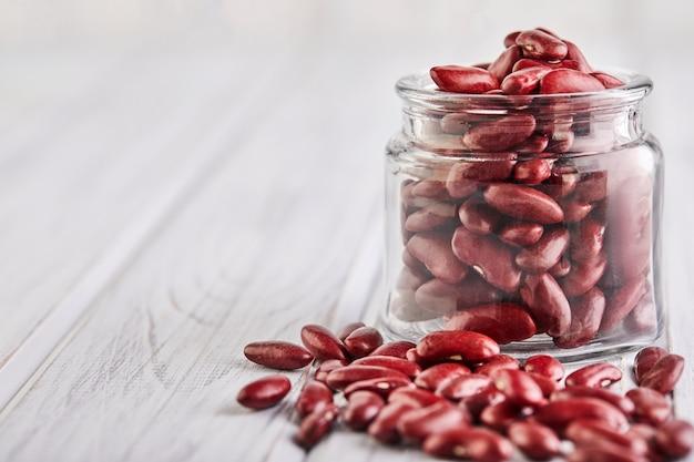 Sementes de feijão vermelho derramadas em uma jarra de vidro
