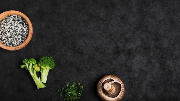 Sementes de gergelim; brócolis; cogumelo; cebola picada no pano de fundo preto textura