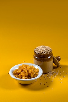 Sementes de gergelim em uma panela de barro com jaggery em uma tigela na superfície amarela