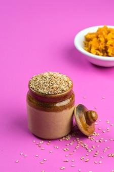 Sementes de gergelim em uma panela de barro com jaggery em uma tigela na superfície rosa
