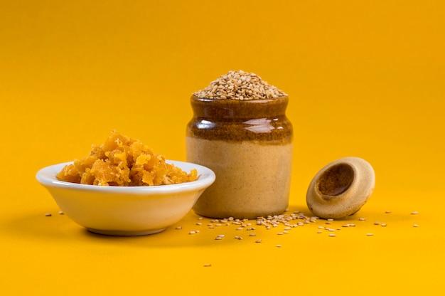 Sementes de gergelim em uma panela de barro com jaggery em uma tigela sobre fundo amarelo