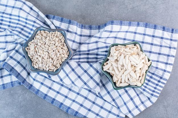 Sementes de girassol brancas em tigelas sobre um pano de prato, na superfície de mármore
