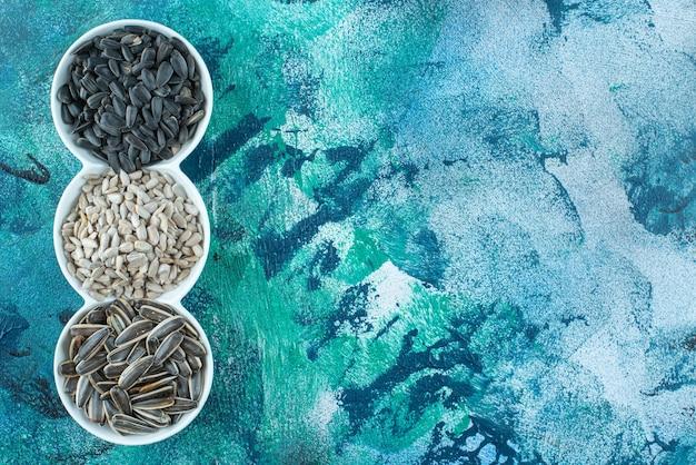 Sementes de girassol descascadas e não descascadas em bandeja na superfície do mármore