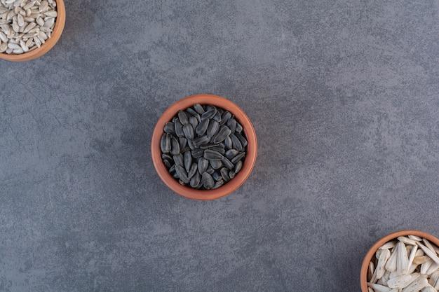 Sementes de girassol diferentes em tigelas, na superfície azul