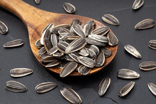 Sementes de girassol em colher em ardósia preta. semente de helianthus