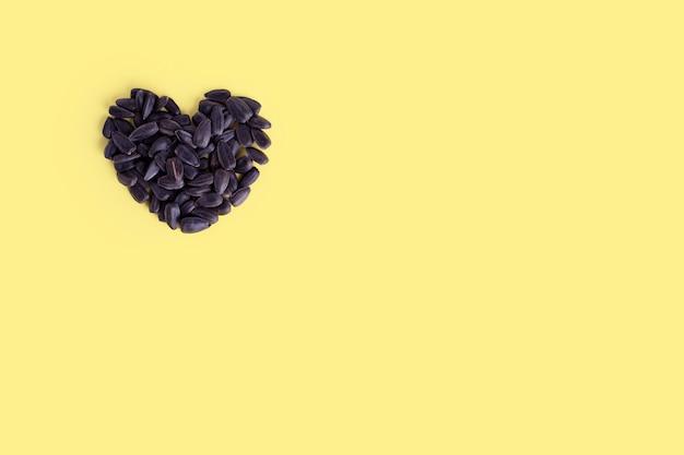 Sementes de girassol em forma de coração torrado no fundo amarelo da moda, cópia espaço, vista superior.