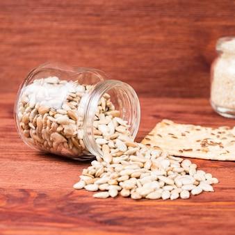 Sementes de girassol em uma jarra com bolos de trigo crocantes em um fundo vermelho de madeira.