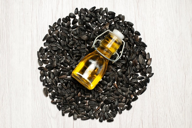 Sementes de girassol frescas de vista de cima sementes coloridas em preto na mesa branca, foto com óleo, lanche, muitas sementes