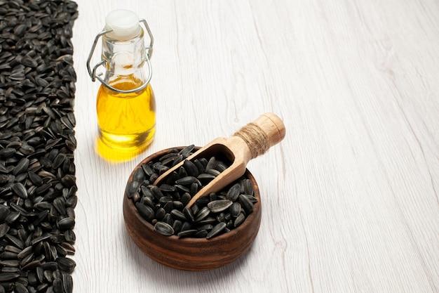 Sementes de girassol frescas de vista frontal sementes coloridas de preto sobre fundo branco sementes de milho, óleo de lanche, foto muitos