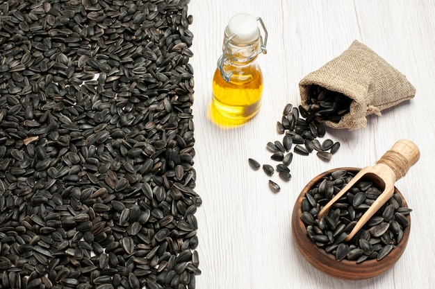 Sementes de girassol frescas de vista frontal sementes coloridas em preto na mesa branca, foto de lanche de sementes oleaginosas, muitos
