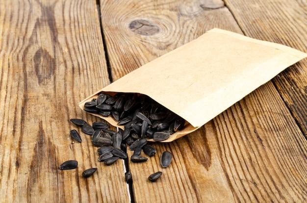 Sementes de girassol pretas com casca em uma sacola artesanal na mesa de madeira