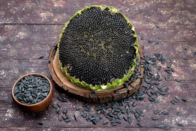 Sementes de girassol pretas frescas e saborosas no fundo marrom óleo de lanche de semente de girassol