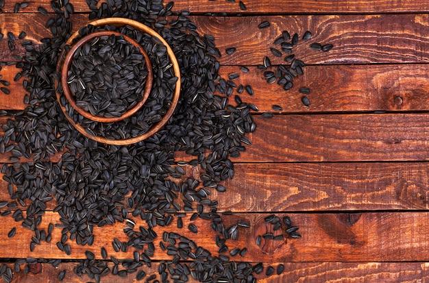 Sementes de girassol pretas no fundo de madeira