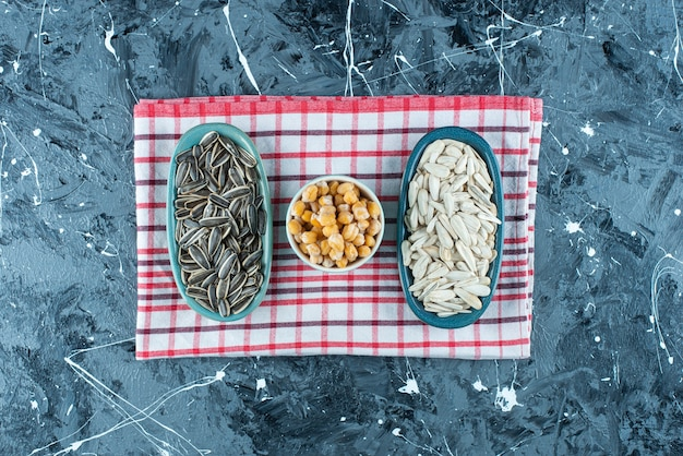 Sementes de grão de bico e girassol em tigelas na toalha de chá em azul.