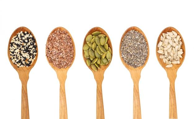 Sementes de grãos orgânicos na colher de pau, semente de chia, gergelim, linho, isolado no fundo branco