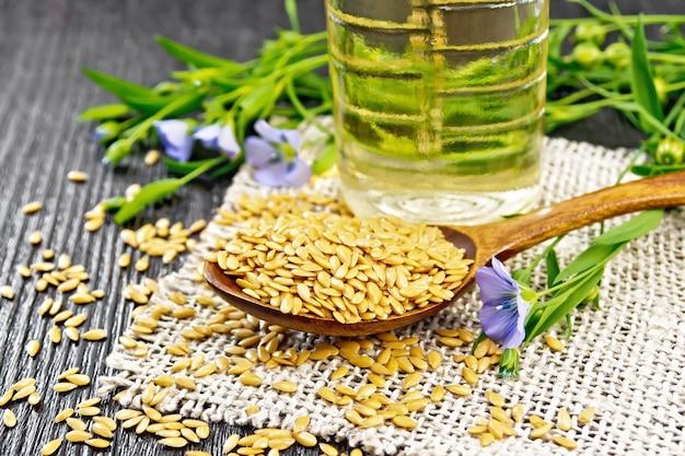 Sementes de linho branco em uma colher, caules de linho com flores azuis e folhas verdes na serapilheira, óleo em uma garrafa no fundo da placa de madeira