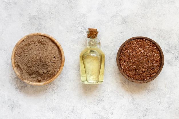 Sementes de linho cruas, farinha e óleo vista de cima na mesa branca