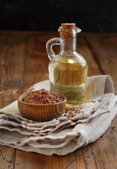 Sementes de linho crus e óleo em uma mesa de madeira fecham
