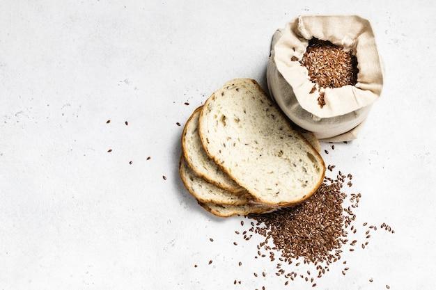 Sementes de linho em um saco, pão fatiado, vista de cima, postura plana.