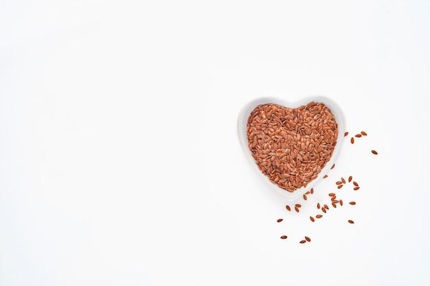 Sementes de linho em uma tigela em forma de coração isolada na mesa branca, vista superior