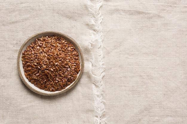 Sementes de linho em uma tigela na toalha de linho natural. vista do topo.