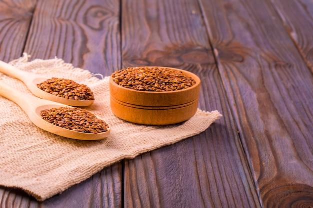 Sementes de linho marrom ou semente de linho em uma tigela pequena na demissão e dois falsos de madeira em uma mesa de madeira marrom