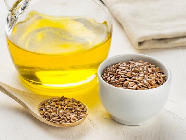 Sementes de linho marrons em colher e óleo de linhaça